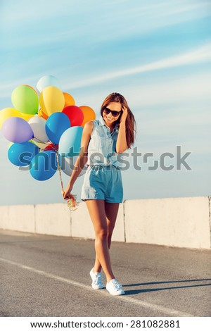 Enjoying great summer day. Smiling young women holding colorful balloons and smiling while walking outdoors  - stock photo