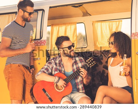 Enjoying great time together. Cheerful young beard man sitting in retro minivan and playing guitar while two his friends looking at him and smiling  - stock photo