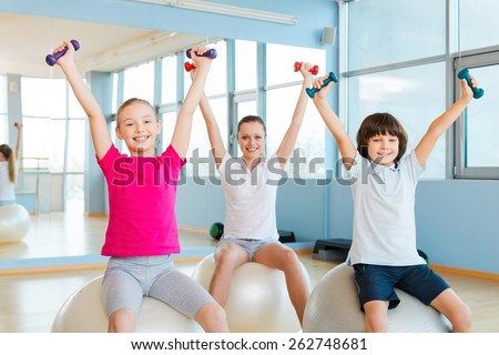 Enjoying healthy lifestyle. Cheerful mother and two children exercising with dumbbells in health club while sitting on the fitness balls  - stock photo