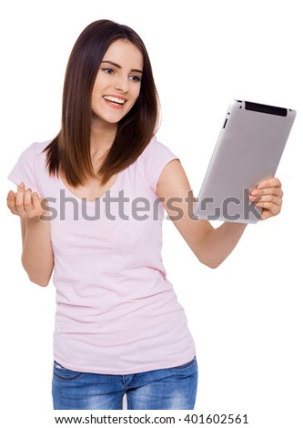 Enjoying her new digital tablet. Beautiful cheerful young woman using her tablet with smile while standing over white background - stock photo