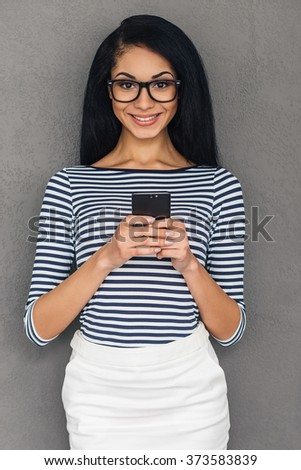 Enjoying her new phone. Attractive young African woman holding smart phone and looking at camera with smile while standing against grey background - stock photo