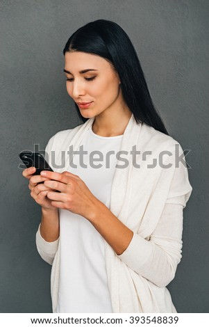 Enjoying her new smartphone. Beautiful young woman using her smartphone while standing against grey background - stock photo
