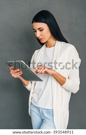 Enjoying her new touchpad. Beautiful young woman using her digital tablet while standing against grey background - stock photo