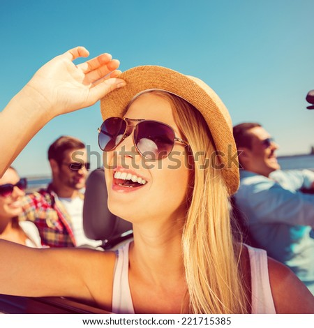 Enjoying her trip. Group of young happy people enjoying road trip in their convertible while beautiful woman adjusting her hat and smiling - stock photo