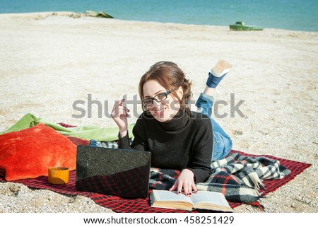 Enjoying her working day. Attractive young woman lying on a comfortable blanket on the beach. Working or studying with laptop and book. - stock photo