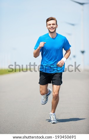 Enjoying his daily jog. Full length front view of handsome young man running along the road and smiling  - stock photo