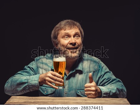 Enjoying his favorite beer.  The front view of handsome smiling  man as fan in denim shirt with glass of beer, sitting at the wooden table - stock photo