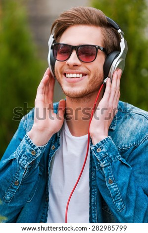 Enjoying his favorite music. Cheerful young man in headphones listening to music and smiling  - stock photo