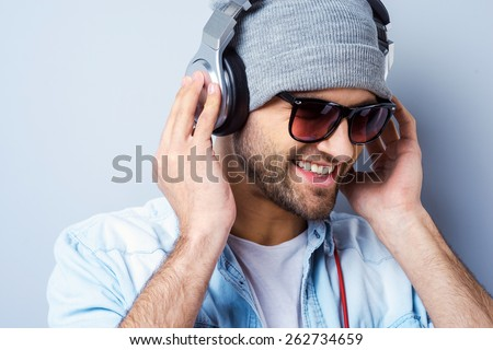 Enjoying his favorite music. Happy young stylish man in hat and sunglasses adjusting his headphones ad smiling while standing against grey background
