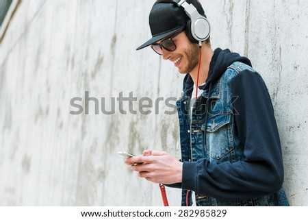 Enjoying his favorite music. Smiling young man in headphones holding mobile phone while leaning at the concrete wall  - stock photo