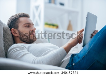Enjoying his leisure time at home. Side view of handsome young man working on digital tablet and looking relaxed while lying on the couch at home - stock photo