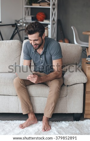 Enjoying his new digital tablet. Handsome young man using his digital tablet with smile while sitting on the couch at home - stock photo