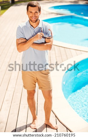 Enjoying his summer vacation. Full length of handsome young man in polo shirt standing by the pool and smiling to you - stock photo