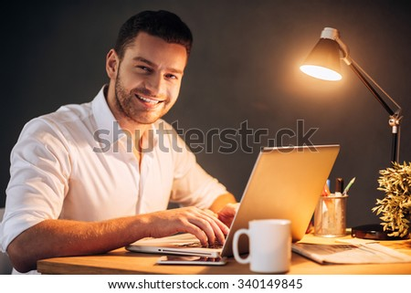 Enjoying his work even at night. Confident young man looking at camera and smiling while sitting at his working place at night time - stock photo