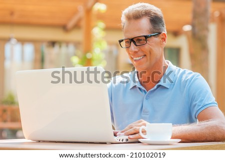 Enjoying his work on fresh air. Cheerful mature man working at laptop and smiling while sitting at the table outdoors with house in the background  - stock photo