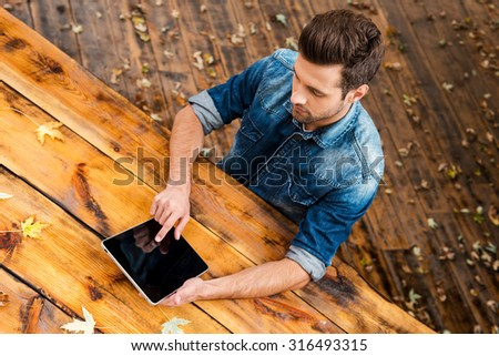 Enjoying his work outdoors. Top view of confident young man working on digital tablet while sitting at the wooden table outdoors - stock photo