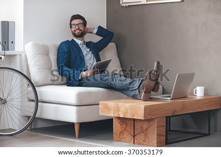 Enjoying his working day. Handsome cheerful young man keeping legs on table and looking away with smile while sitting on the couch in office - stock photo