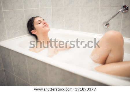 Enjoying home spa relaxation after hard day.Young woman takes bubble bath.True bliss.Total relaxation.Blissful moments.Spa treatments for skin rejuvenation.Personal hygiene.Woman skin and body care - stock photo