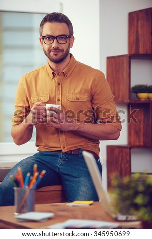 Enjoying hot and fresh coffee. Confident young man holding coffee cup and looking t camera while sitting at his working place in office - stock photo