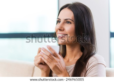 Enjoying hot coffee. Attractive young woman drinking coffee and smiling while relaxing on the couch at home  - stock photo