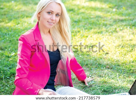 Enjoying learning. Beautiful student girl holding books and smiling at the camera while sitting on the grass against the building of the university. - stock photo
