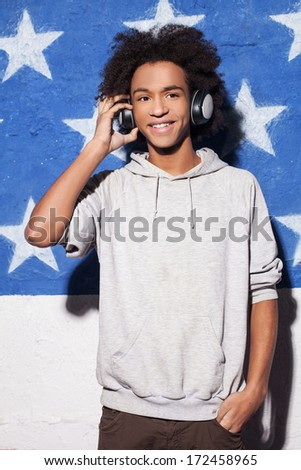 Enjoying music. Cheerful young African man in headphones standing against American flag and listening to the music - stock photo