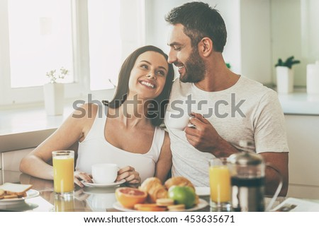 Enjoying nice morning together. Beautiful young couple bonding to each other and smiling while sitting in the kitchen together and having breakfast - stock photo