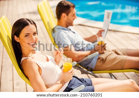 Enjoying orange fresh poolside. Side view of beautiful young couple sitting at the deck chairs by the pool while woman looking at camera and smiling - stock photo
