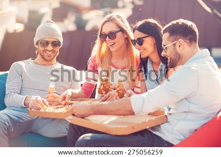 Enjoying pizza together. Four young cheerful people eating pizza and drinking beer while sitting at the bean bags on the roof of the building - stock photo