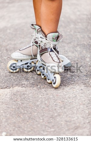 Enjoying roller skating rollerblading on inline skates sport in park. Outdoor activities. Part of human legs in sport shoes. - stock photo