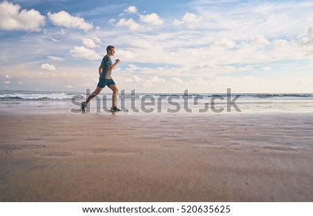 Enjoying sports lifestyle. Happy young man in headphones jogging on the sea shore.