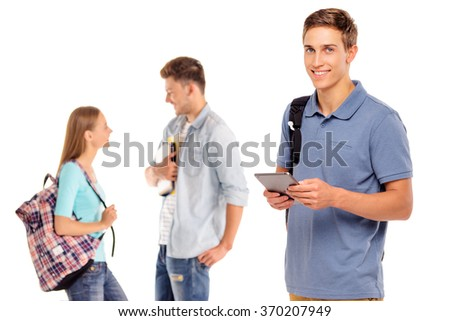 Enjoying student life. Handsome young man using tablet computer and smiling with his friends talking in the background. Isolated on white. - stock photo