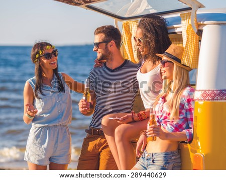 Enjoying summer day with friends. Group of cheerful young people discussing something and smiling while standing near their retro minivan with sea in the background - stock photo