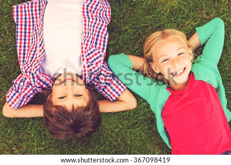 Enjoying summer together. Top view of two cute little children holding hands behind head and smiling while lying on the green grass together - stock photo