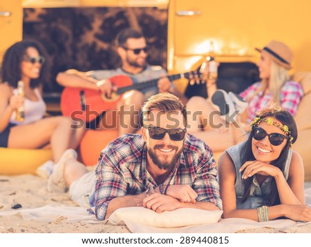 Enjoying summer with friends. Cheerful young couple smiling and looking at camera while lying near retro minivan with friends in the background - stock photo