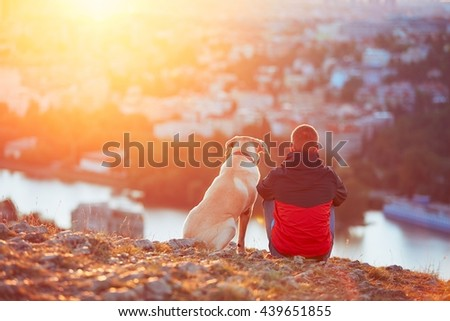 Enjoying sun. Pensive young man sitting on the hill with his dog (yellow labrador retriever). Amazing sunrise in the city. Prague in Czech Republic. - stock photo