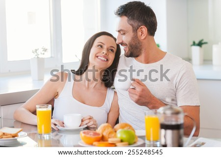 Enjoying Sunday morning together. Beautiful young couple bonding to each other and smiling while sitting in the kitchen together and having breakfast  - stock photo