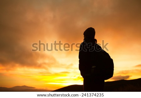 Enjoying sunrise from the top of the mountain - stock photo
