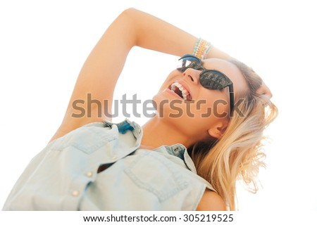 Enjoying sunshine. Low angle view of cheerful young woman holding hand in hair and smiling while standing outdoors - stock photo