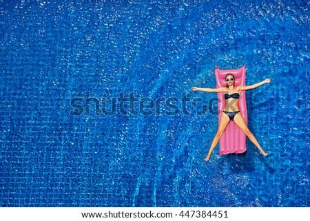 Enjoying suntan. Vacation concept. Top view of slim young woman in bikini on the pink air mattress in the big swimming pool. - stock photo