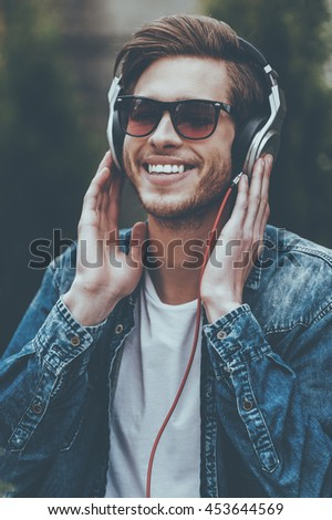 Enjoying that song! Cheerful young man in headphones listening to music and smiling - stock photo