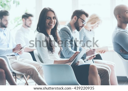 Enjoying the conference. Side view of group of young people sitting on conference together and making notes while one woman looking at camera and smiling - stock photo