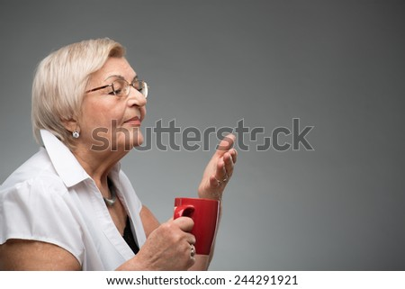 Enjoying the cup of coffee. Happy senior woman smelling the cup of coffee looking at copy space while standing against grey background - stock photo
