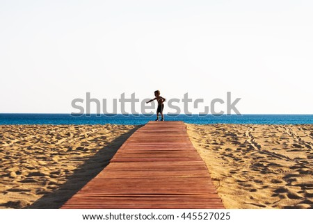 Enjoying the freedom! - Little boy dancing happily on a wooden path on the beach.