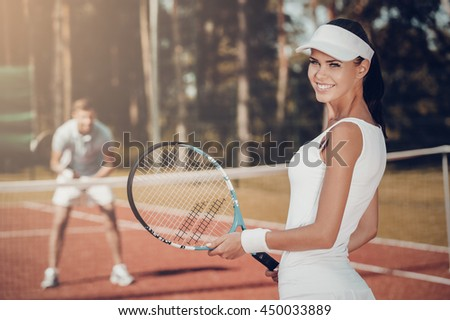 Enjoying the game. Beautiful young woman holding tennis racket and looking over shoulder with smile while man in sports clothing standing in the background - stock photo