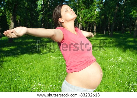 Enjoying the nature. Young pregnant woman arms raised enjoying the fresh air in green forest. - stock photo