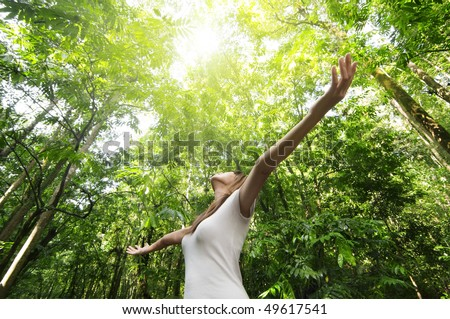 Enjoying the nature. Young woman arms raised enjoying the fresh air in green forest. - stock photo