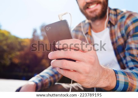 Enjoying the rhythm of his life. Close-up of handsome young bearded man smiling while listening to music - stock photo