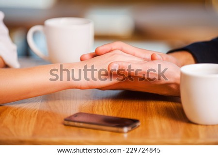 Enjoying their closeness. Close-up of couple holding hands while enjoying fresh coffee in cafe together - stock photo