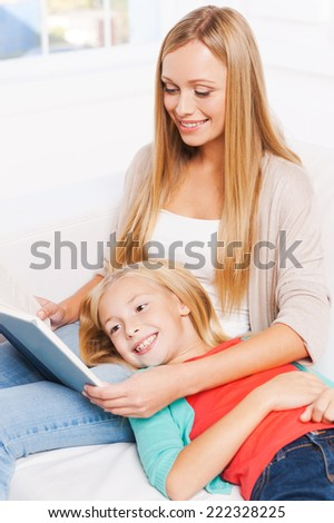 Enjoying their favorite book together. Top view of happy mother and daughter reading together while sitting on the couch at home together - stock photo